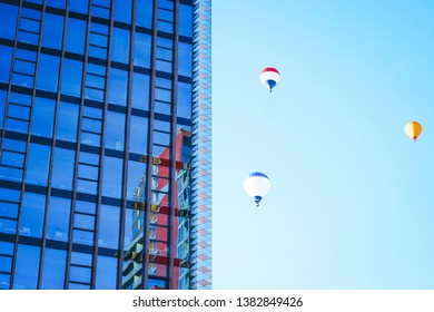 Air balloons and architecture of modern metal and glass skyscraper reflecting the blue sky