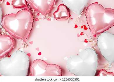 Luchtballonnen van hartvormige folie op pastelroze achtergrond. Liefde concept. Feestdagen. Valentijnsdag of bruiloft/vrijgezellenfeest decoratie. Metalen ballon