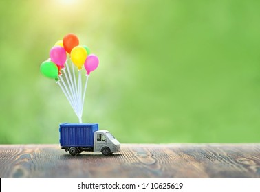 air balloons and truck toy on wood background. truck, Concept for visualization of delivery services, logistics, business, forwarding, travel, cargo delivery. banner, copy space