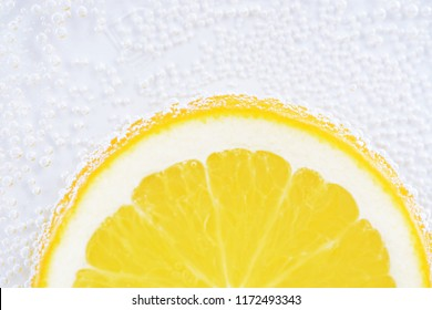 Air bubbles form on an orange peel with an orange in the carbonated water in front of white background - Close-up of an orange in the water
