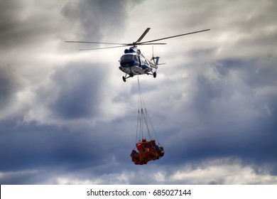 Air cargo and aviation work, cargo air service, lift helicopter. Helicopter carries sling (rope mesh) with metal barrels