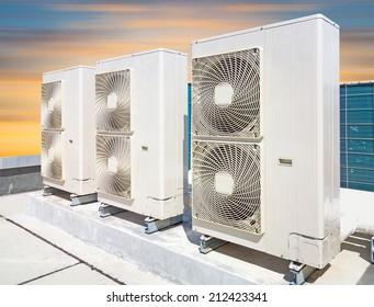 Air compressor machine on pedestal with sky background.