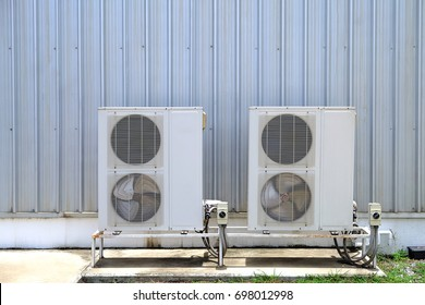 Air compressor machine part of air conditioner system, Air compressor on concrete pedestal with siding wall background.