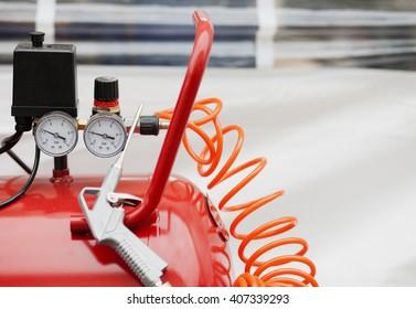 Air compressor system: manometer, cable, gun and accessories, closeup.