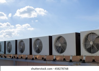 Air compressors on roof of factory with blue sky background.