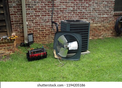 Air Conditioner compressor condenser coil with fan and tools being worked on next to a brick house for repair maintenance.