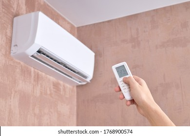 air conditioner at domestic room. heat temperature indoors. person holds remote control for aircon. heat or cold at home.