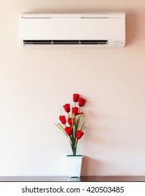 Air conditioner and flower vase with wall.