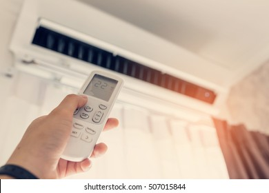 Air conditioner inside the room with woman operating remote controller. / Air conditioner with remote controller