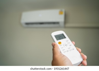 Air conditioner inside top the room man operating remote controller open air conditioner energy savings
