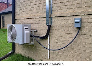 Air Conditioner mini split system next to home with painted brick wall and space for text copy