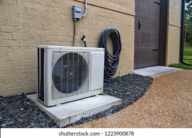 Air Conditioner mini split system next to home with painted brick wall