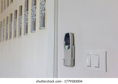 air conditioner remote control attached to white wall with an electrical switch inside the house