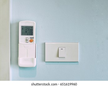 Air conditioner remote control and electrical switch on wall.