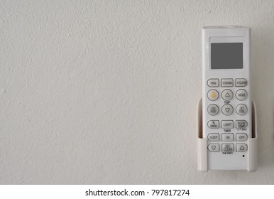 Air conditioner remote control on white paint wall background with copy space