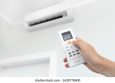 Air conditioner split on the wall inside the room. Man hand holding remote control