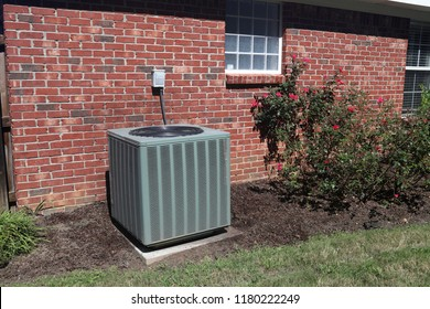 Air Conditioner system next to a home, with rose bushes and brick wall.