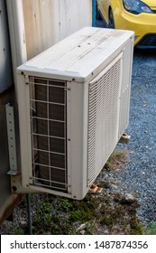 The air conditioner that is installed outside is old and rusty, waiting for maintenance.