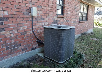 Air Conditioner Unit next to brick wall of house