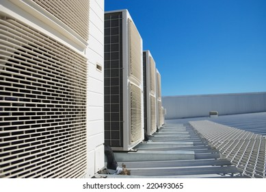 Air Conditioner units (HVAC) on the roof of an industrial building. Blue sky in the background. No people. Copy space.