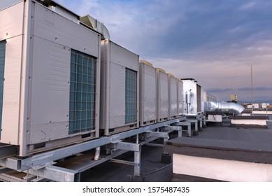Klimaanlagen VRV (HVAC), großer Ventilator und ein Wasserkühler auf dem Dach eines neuen Industriegebäudes mit blauem Himmel und Wolken im Hintergrund.