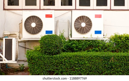 Air Conditioner at the windows  wall background  and Green Tree fence
