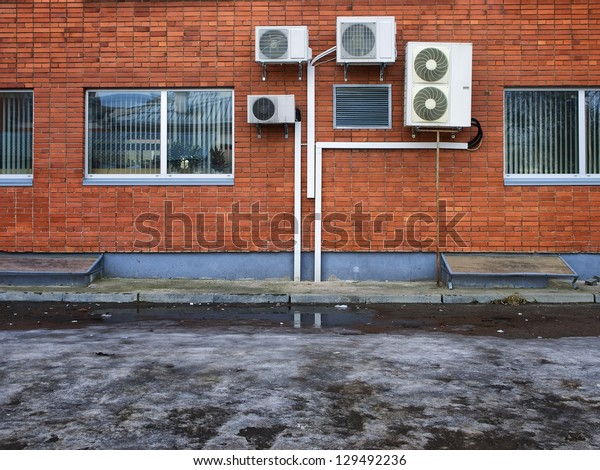 air conditioners on a red brick wall