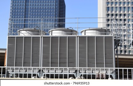 Air conditioning cooling towers in front of buidlings with fins to the front