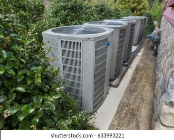Air conditioning and heating units for a big residential house hidden by holly