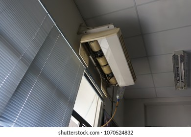 Air conditioning in the old broken and plastic bottle support leaking water take away through the window.