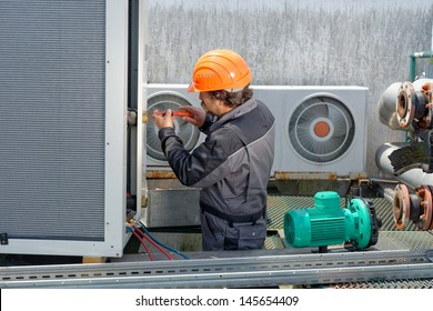 Air Conditioning Repair, repairman on the roof fixing huge air conditioning system. Model is actual electrician.