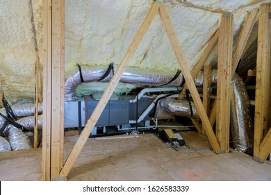 Air conditioning system attached to attic thermal foam plastic insulation new home installation of HVAC tubing vents heating system on the roof