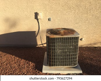 Air conditioning unit machine outside stucco red rock southwest hot heat summer bills energy conservation use electric cool heat rusty old new