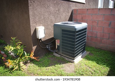 Air conditioning unit outside of stucco home backyard
