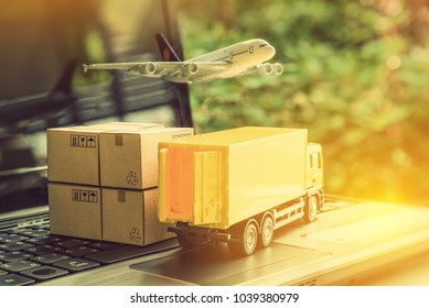 Air courier / freight forwarder or shipping service concept :  Boxes, a truck, white plane flies over a laptop, depicts customers order things from retailer sites via the internet and ship worldwide.