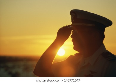AIR CRAFT CARRIER, NEW YORK - CIRCA 1986: Military officer saluting at sunset, NY