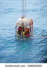 Air divers lowered down by LARS in a cage to perform subsea work.