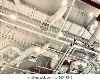 Air duct, wiring and plumbing in the mall. Air conditioner pipe, wiring pipe, and plumbing pipe system. Building interior concept. Ceiling lamp light with opened light. Interior architecture concept.