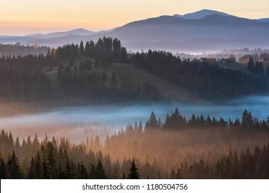 The air. Early morning fog over the autumn slopes of Carpathian Mountains (Yablunytsia village and pass, Ivano-Frankivsk oblast, Ukraine).