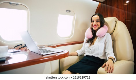 In the air. An extremely beautiful woman in formal attire is flying business class, smiling and relaxing in her window seat during the flight.