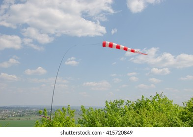 Air field direction sign and a wind force windsock against the  blue sky with clouds.