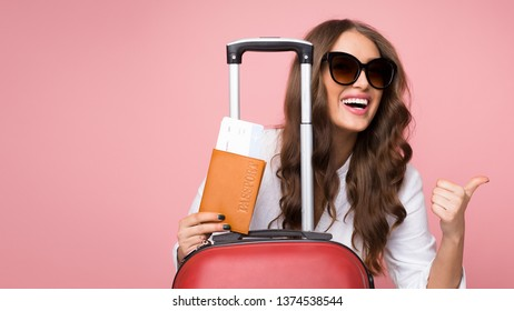 Air flight journey. Woman with suitcase showing thumb up over pink background