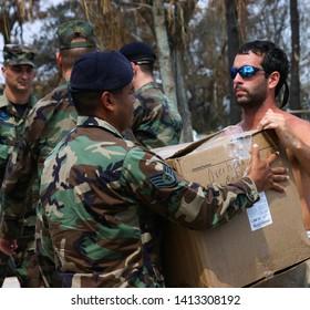 Air Force Staff Sergeant hands medical supplies to Hurricane Katrina survivor. Taken at Biloxi, MS on September 5, 2005.
