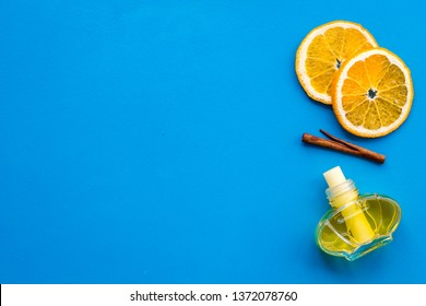air freshener sticks with cinnamon and orange on blue background top view mockup