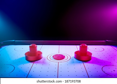 Air hockey table with dramatic lighting on a dark background