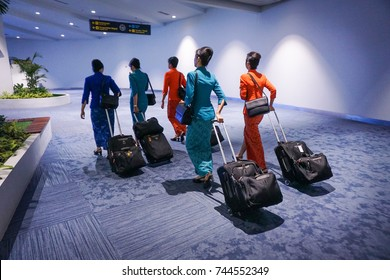 air hostess in international airport, walking with her luggage, back view. Flight attendant going to meet her crew
