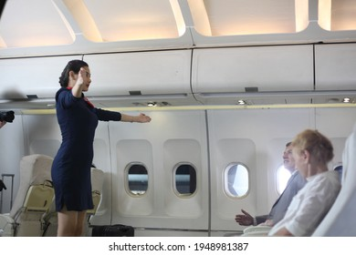 Air hostess or stewardess service , Young slim and attractive woman stewardess and background of plane, Asian flight attendant posing with smile at middle of the aisle inside aircraft passenger seat
