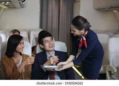 Air hostess or stewardess service , Young slim and atractive woman stewardess and background of plane, Asian flight attendant posing with smile at middle of the aisle inside aircraft passenger seat
