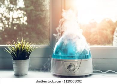 Увлажнитель воздуха во время работы. Белый увлажнитель увлажняет сухой воздух. Улучшение комфорта проживания в доме, квартире. Улучшение благосостояния людей.