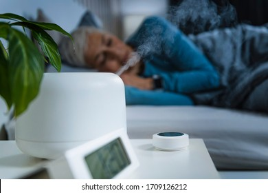 Air Humidifier increasing the humidity in a bedroom for better sleep. Beautiful mature woman sleeping in bed.